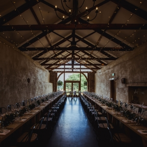 The Cider barn at Upton Barn laid for a wedding breakfast with twinkly lights