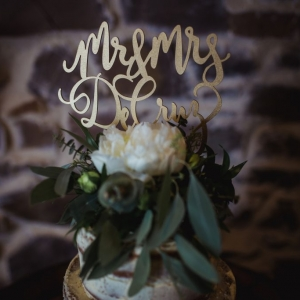 Wedding cake topper in gold reads Mr & Mrs DeCruz