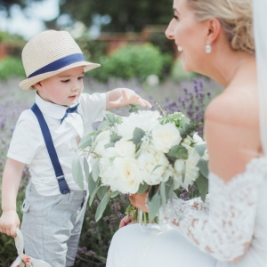 Page boy looks at brides bouquet