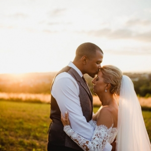 Bride and groom kiss the field
