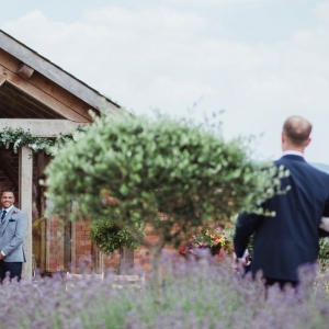 Bride is walked down the aisle by her father in the Walled Garden at Upton Barn
