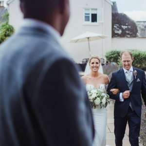 Bride walks with her father down the aisle of the Walled garden to met her beau
