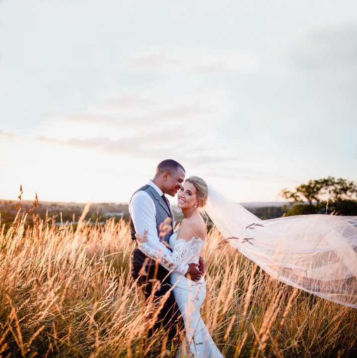 Bride and groom smile while they embrace the field