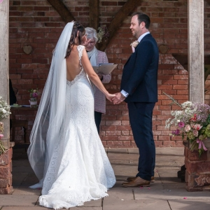 Bride wipes away a tear at civil ceremony in the arbour of Upton Barns Walled Garden