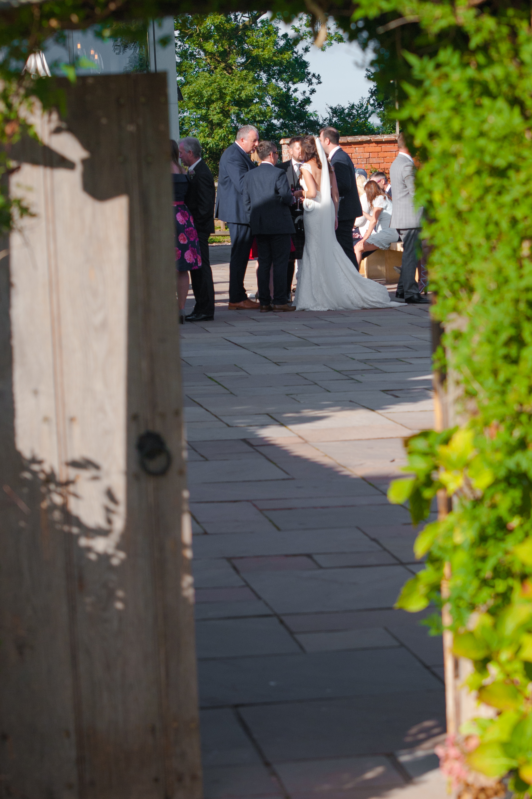 Wedding party viewed through the gate of the walled garden