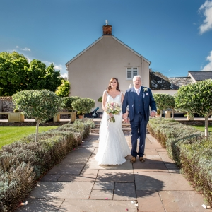 Bride is walked by her father down the aisle of the Walled garden at Upton Barn