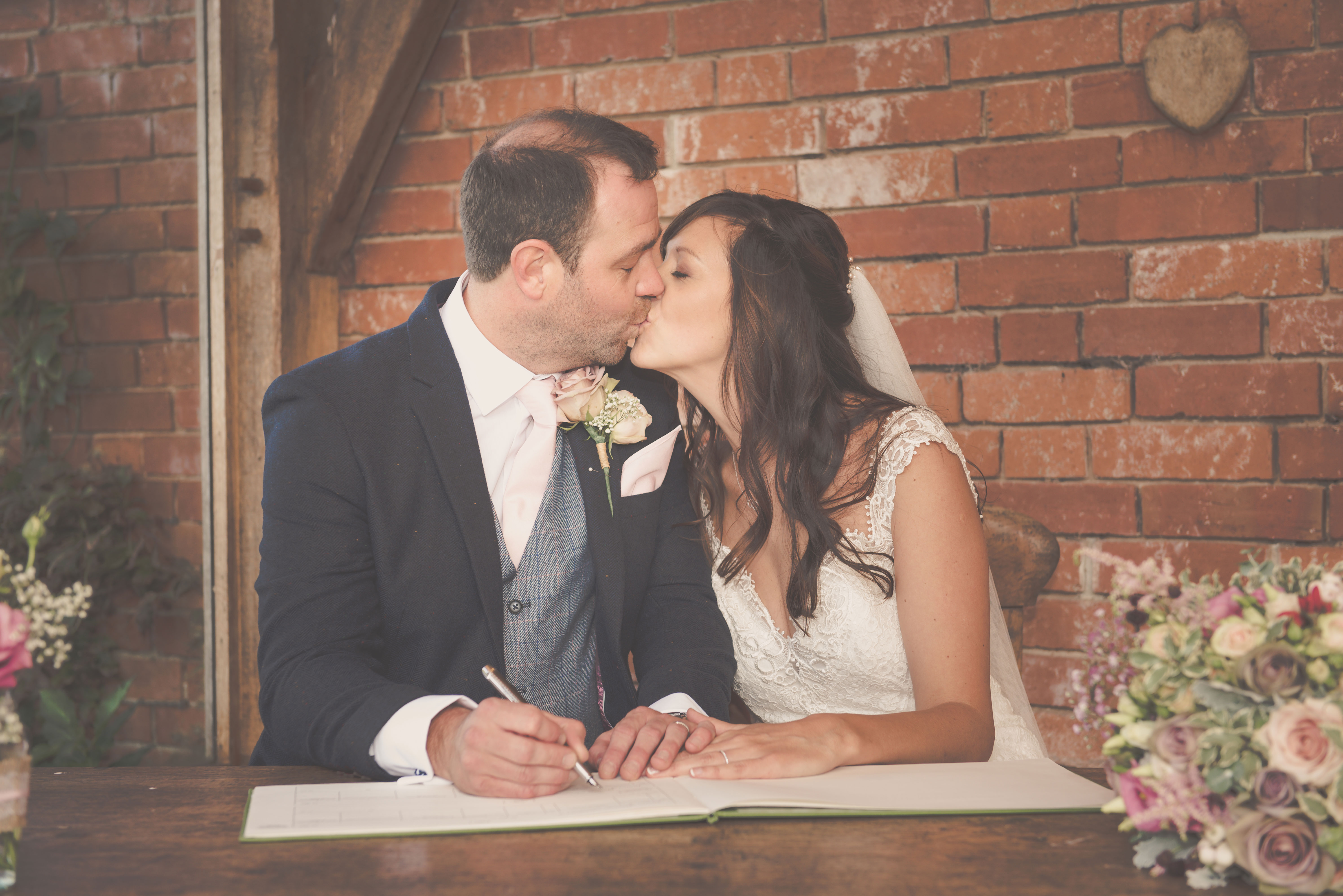Bride and Groom kiss at signing of the register
