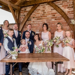 Wedding party gather round table in the arbour of Upton Barns Walled Garden