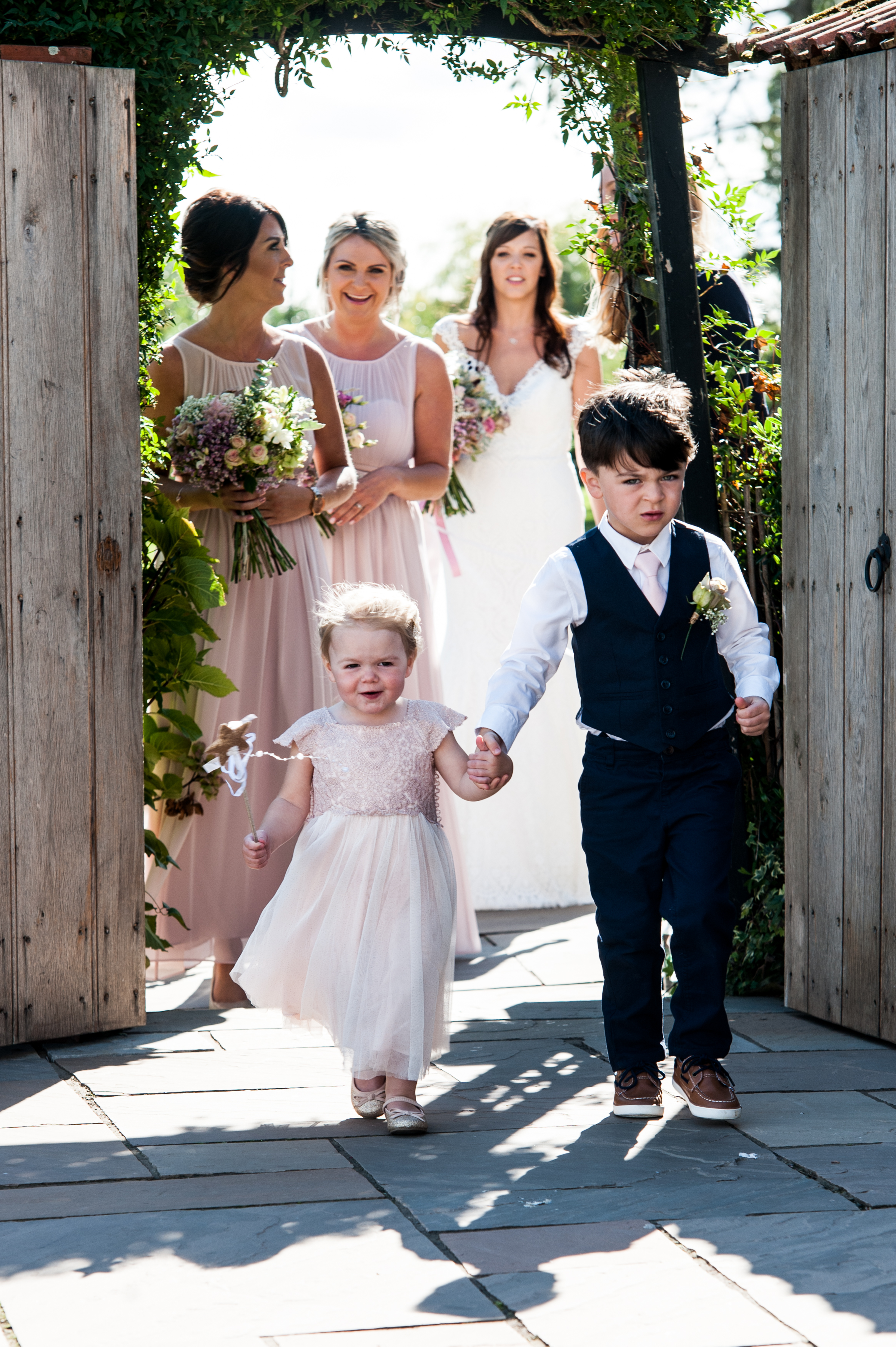 Flower girl and page boy make their entrance through the walled garden gate