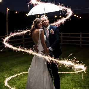 Bride and groom surrounded by sparklers in the garden at night