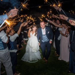 Bride and groom under a sparkler guard of honor