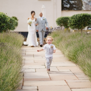 Page boy runs ahead of bride an her father walking down the aisle of the Walled Garden at Upton