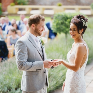 Groom places the ring on the brides hand in garden ceremony