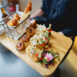 Close up of exquisite canapes served to guests on a wooden board