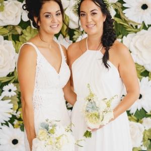 Bride and bridesmaid pose by floral backdrop