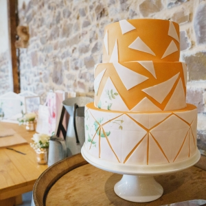 Wedding cake and guests books on tables in the Press Bar at Upton Barn & Walled Garden