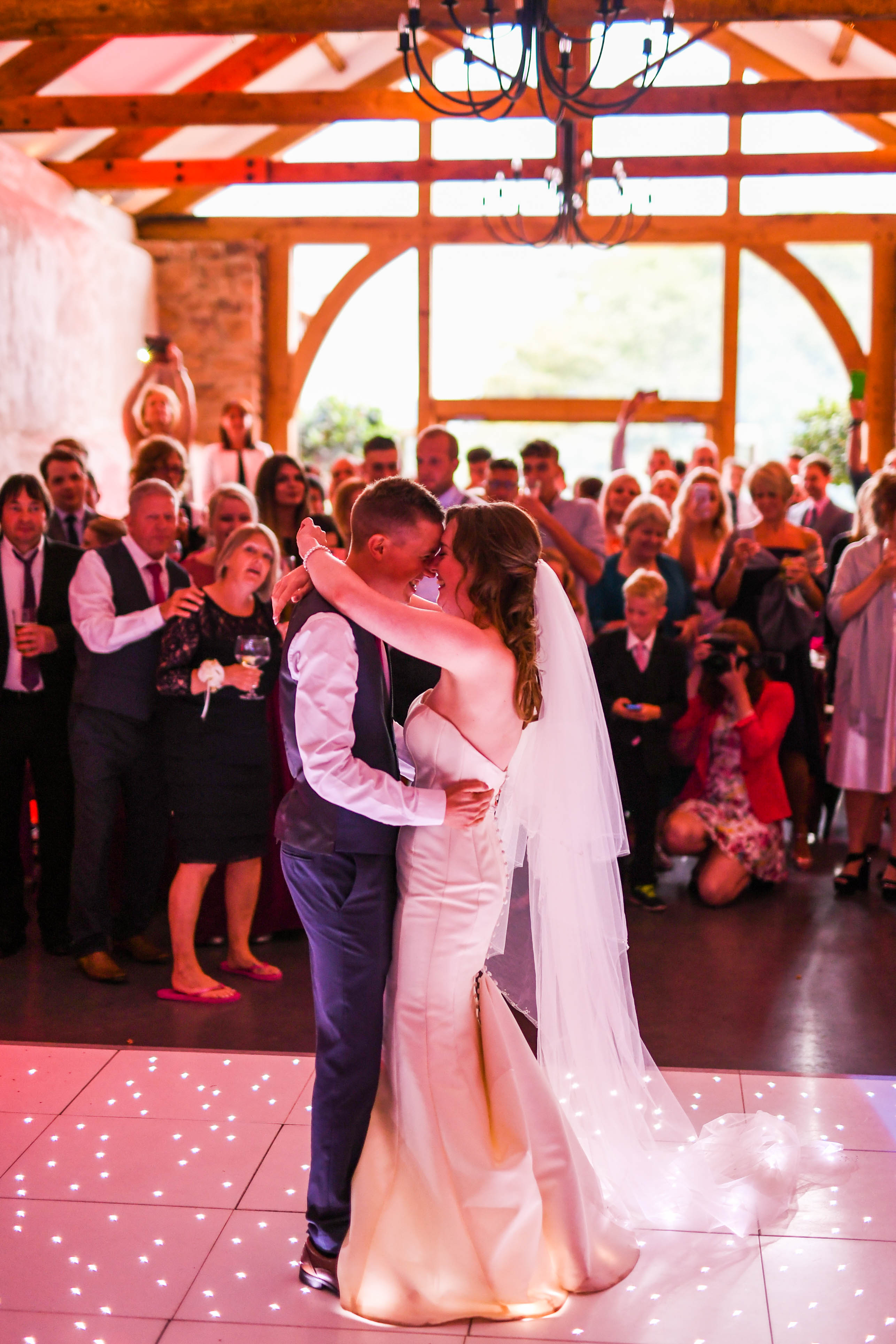 Bride and Groom take their first dance in the Cider Barn on a sparkly dancefloor