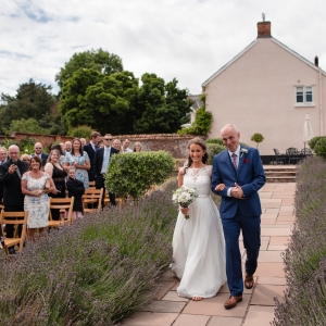 Bride is walked by her father down the aisle at Upton Barn & Walled Garden