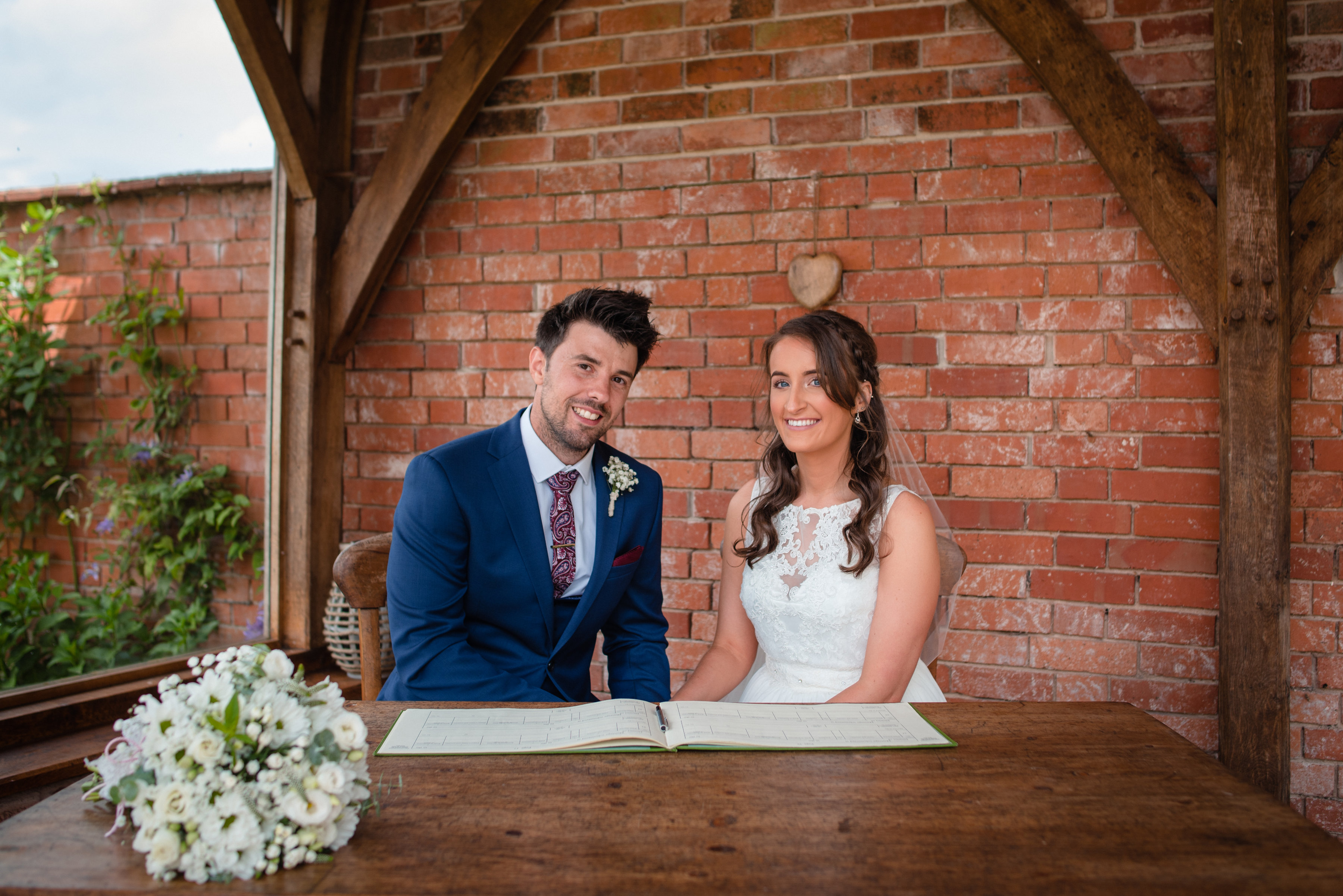 Bride and groom sign the registar at Upton Barn & Walled Garden