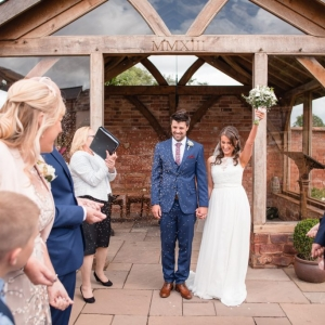 Confetti covers the bride and groom at the arbour at Upton Barn & Walled Garden