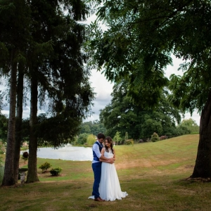 Bride and groom embrace beside the lake at Upton Barn & Walled Garden