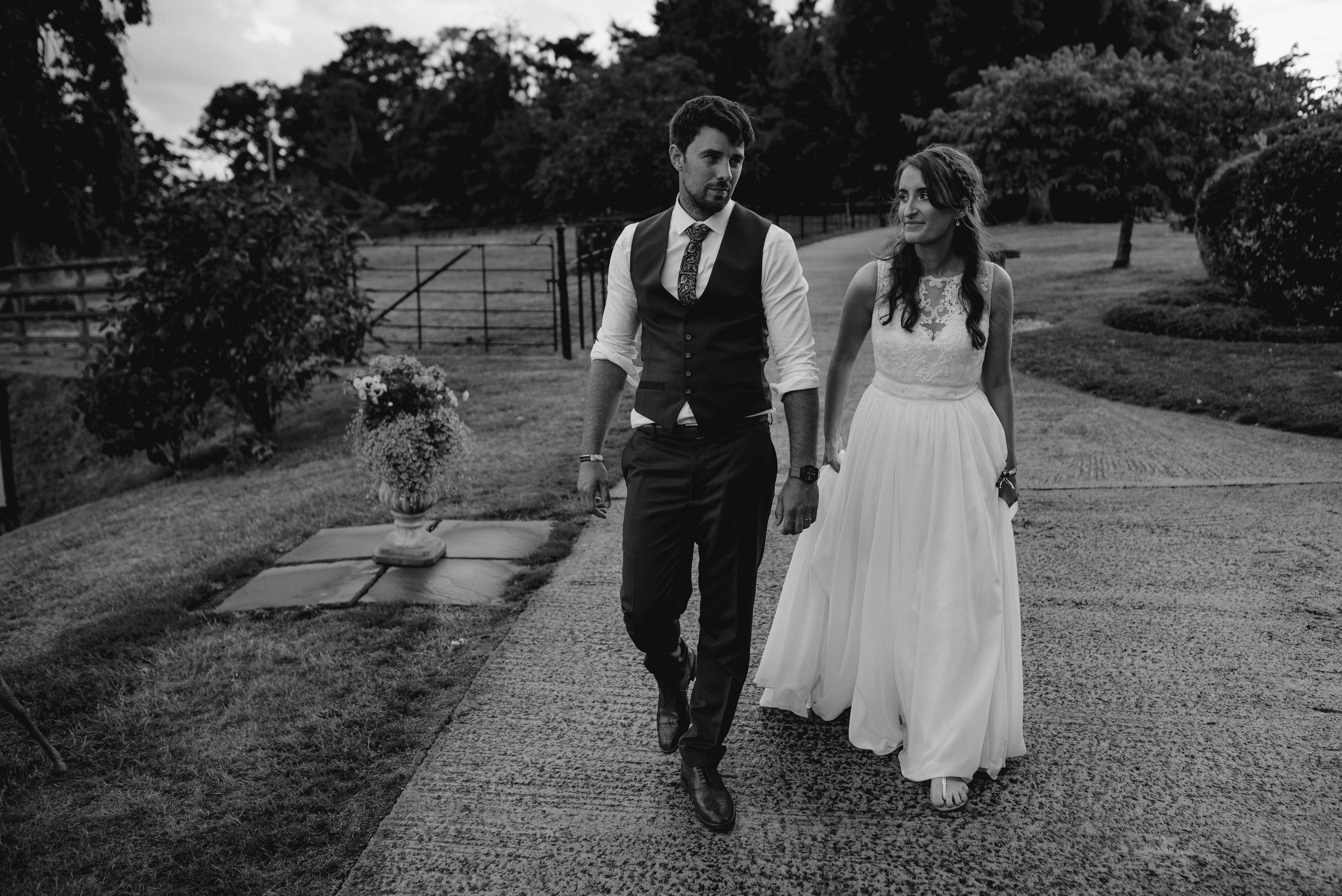 The bride and groom walk doewn the drive at Upton Barn & Walled Garden