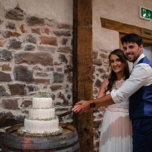 Bride and groom cut their wedding cake at Upton Barn & Walled Garden