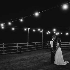 Newly weds hold hands under the festoon lights at Upton Barn & Walled Garden
