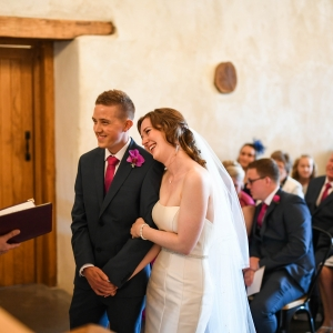 Bride and groom exchanging vows inthe Cider Barn at Upton Barn & Walled Garden