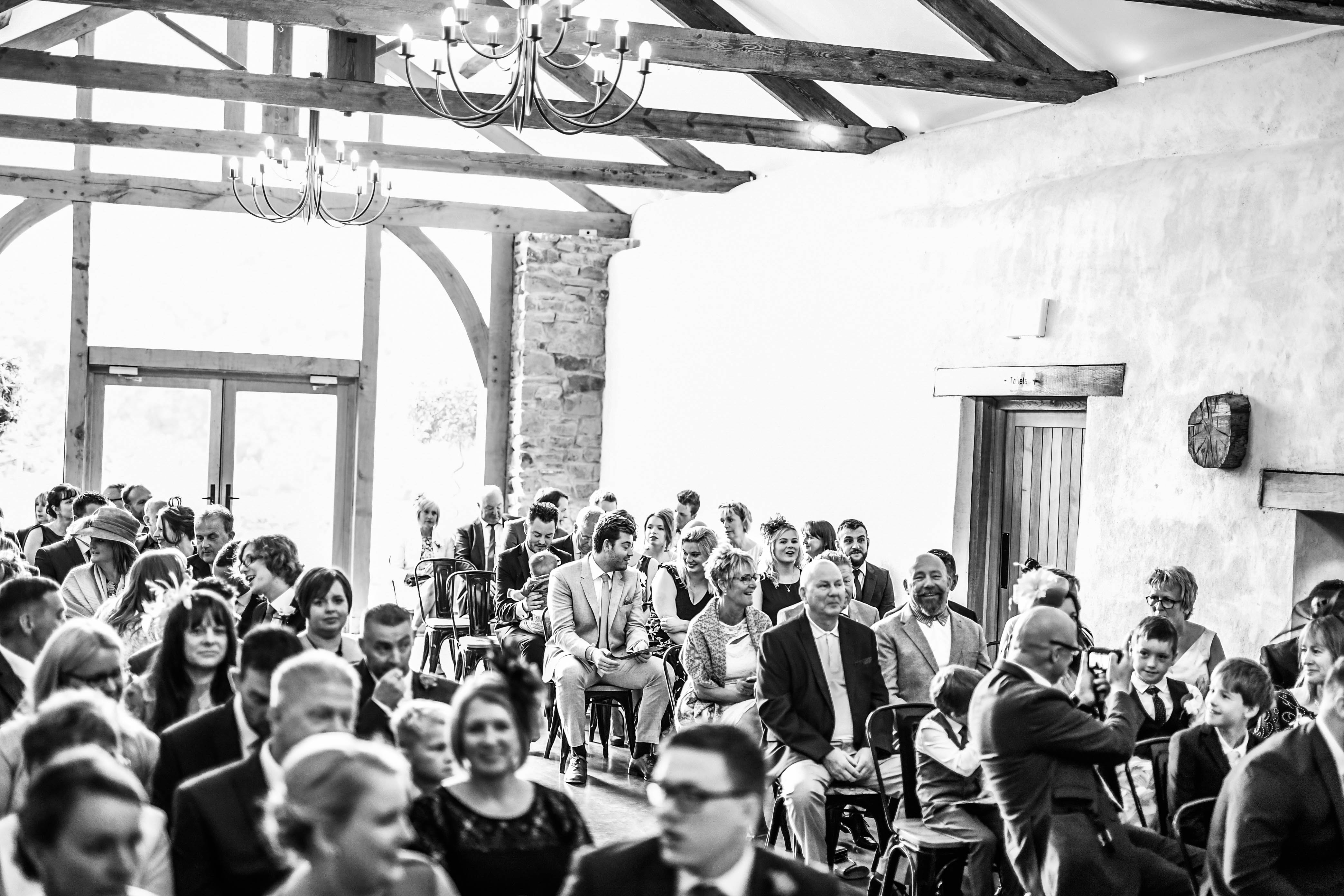 Guests await the arrival of the bride at Upton Barn & Walled Garden