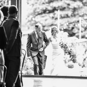 Bride is escorted by her father up the steps into the Cider Barn