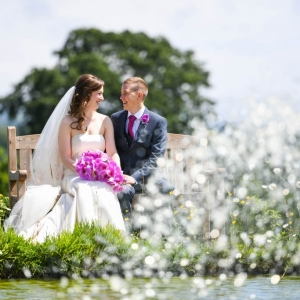 Bride and groom seated on a bench by the fountain