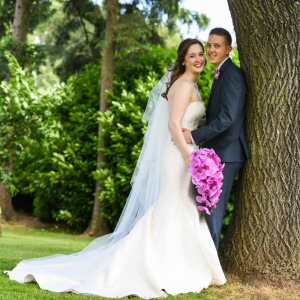 Bride and groom embrace under the trees in the grounds of Upton Barn