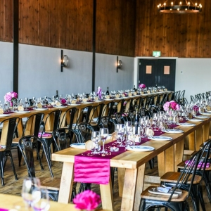 Trestle tables laid for wedding breakfast in the Stable Barn