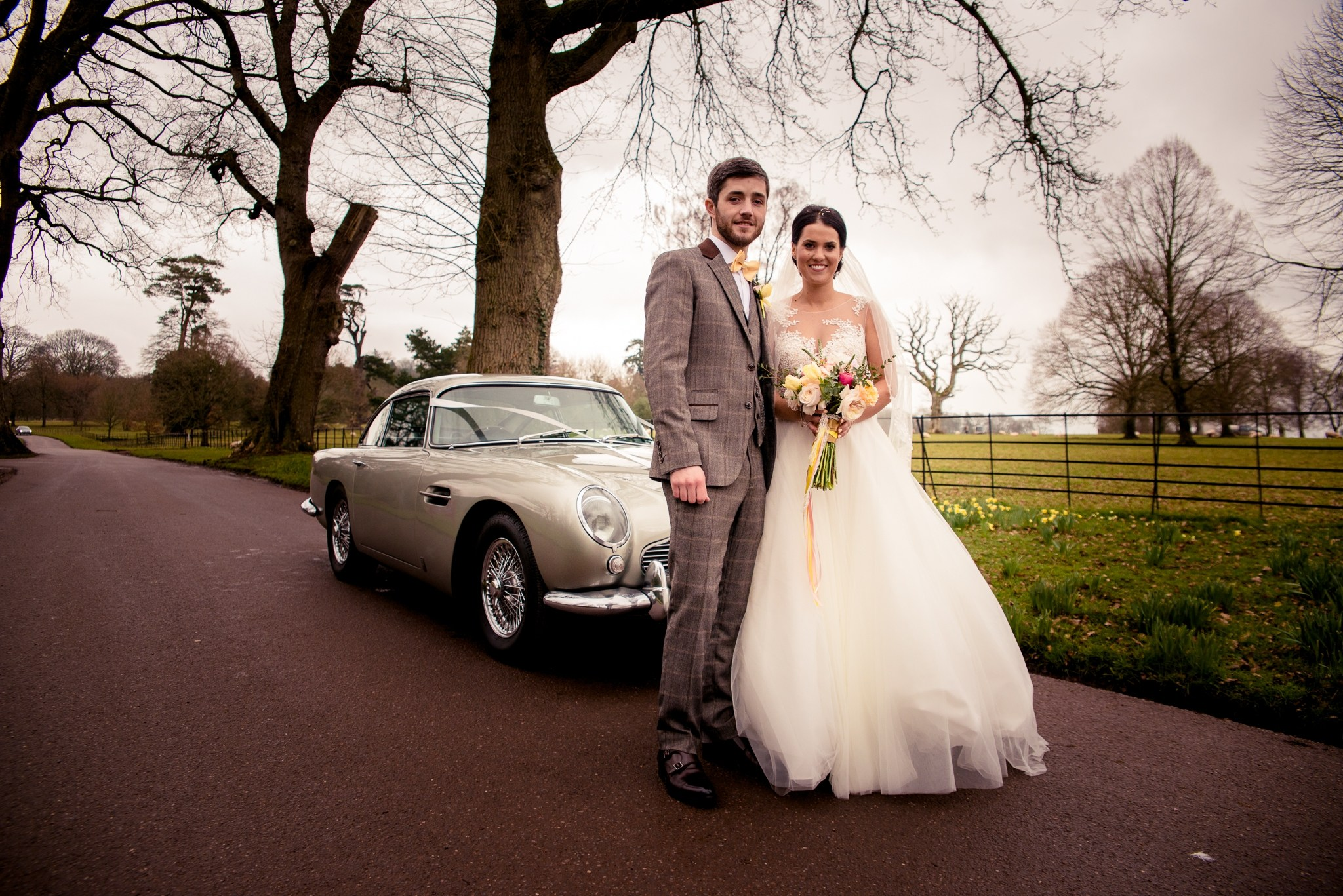 Bride and groom arrive by vintage car to Upton Barn & Walled Garden
