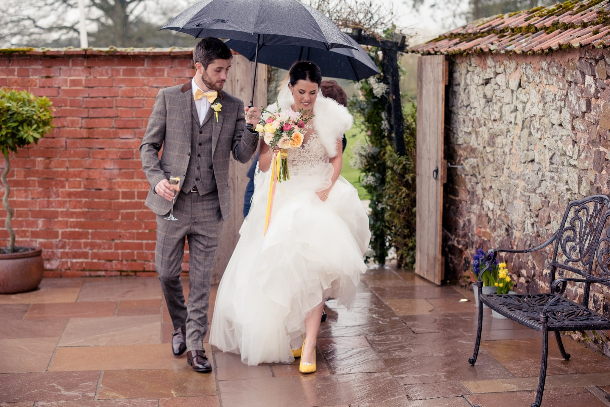 Bride and groom walk through the gate into the walled garden