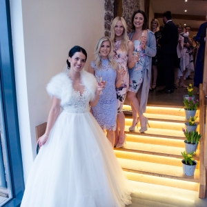 Bride and friends gather on the lit steps of the Press Bar