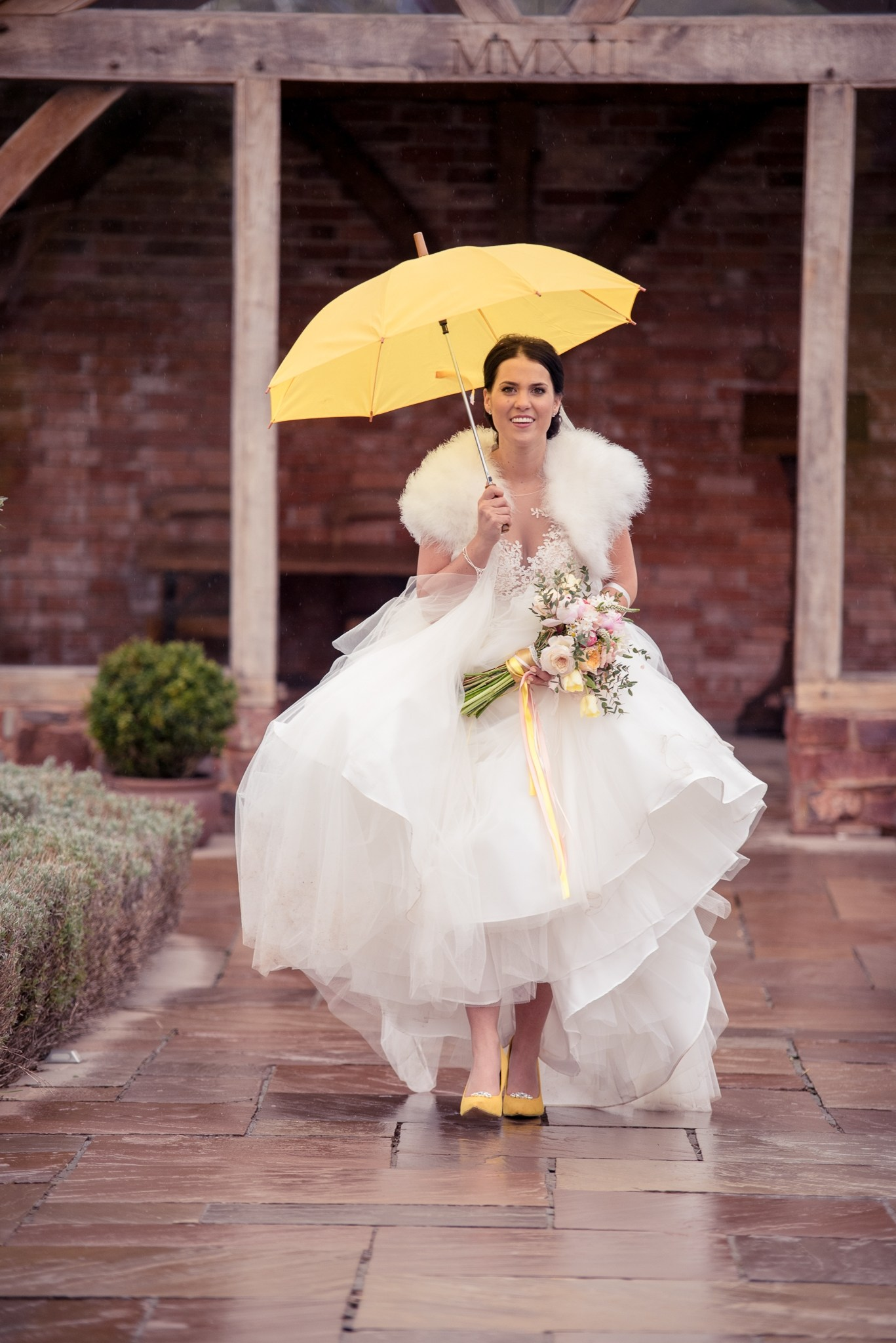 Bride with bright yellow umbrella walks the aisle in the walled garden
