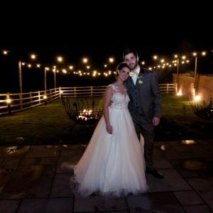 Bride and groom hug in front of the fire pits and festoon lights