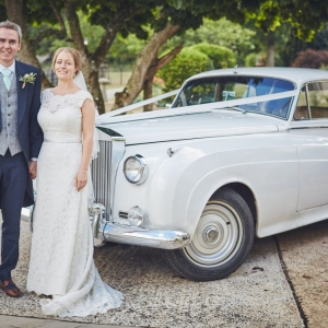 Bride and groom stand beside old Rolls Royce at Upton Barn & Walled Garden