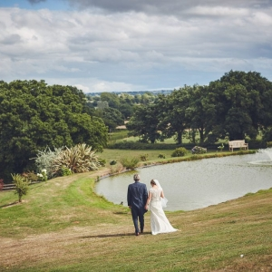 Bride and groom walk by the lake at Upton Barn & Walled Garden