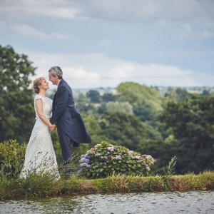 Couple kiss besides the lake at Upton Barn & Walled Garden