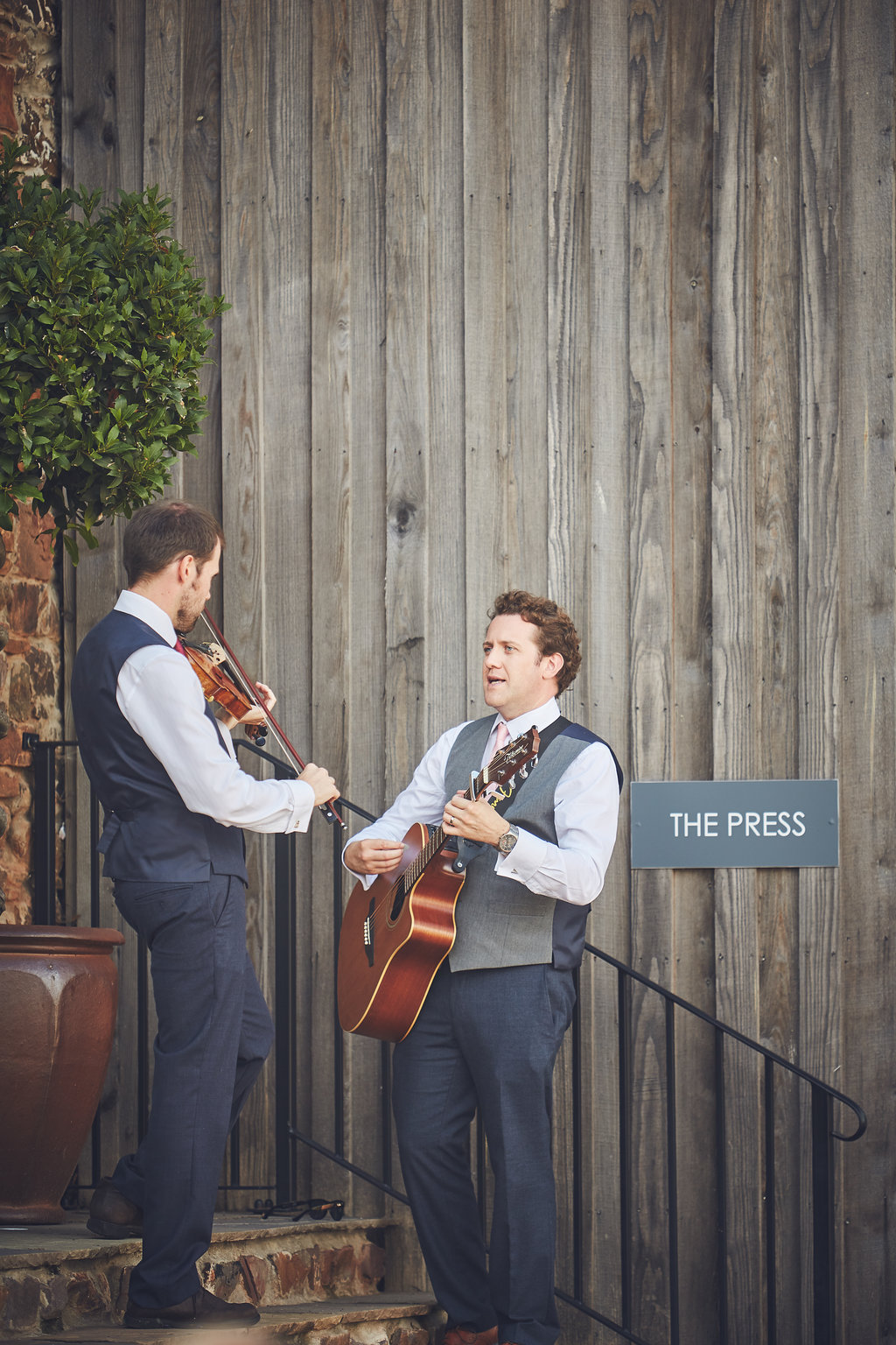 Guitarist and violinist play outside The Press bar at Upton Barn & Walled Garden
