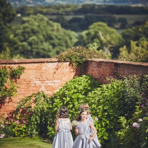 Young bridesmaids play in the Walled Garden at Upton Barn