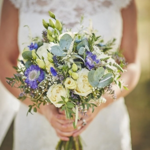 Close up of brides bouquet with blue and cream blossoms