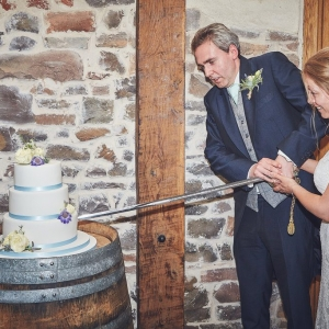 Bride and groom cut the wedding cake with a ceremonial sword at Upton Barn & Walled Garden