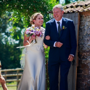 Bride and her father enter through the gate into the walled garden at Upton Barn & Walled Garden