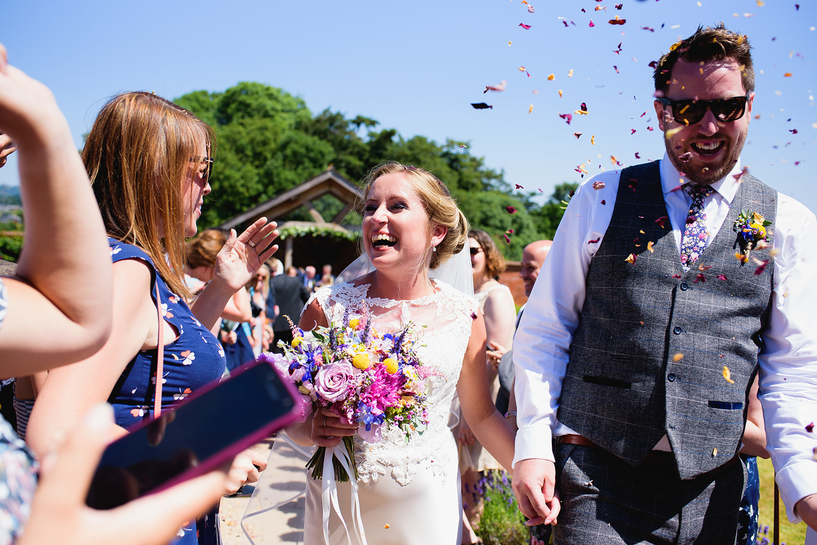 Confetti covers the bride and groom at Upton Barn & Walled Garden