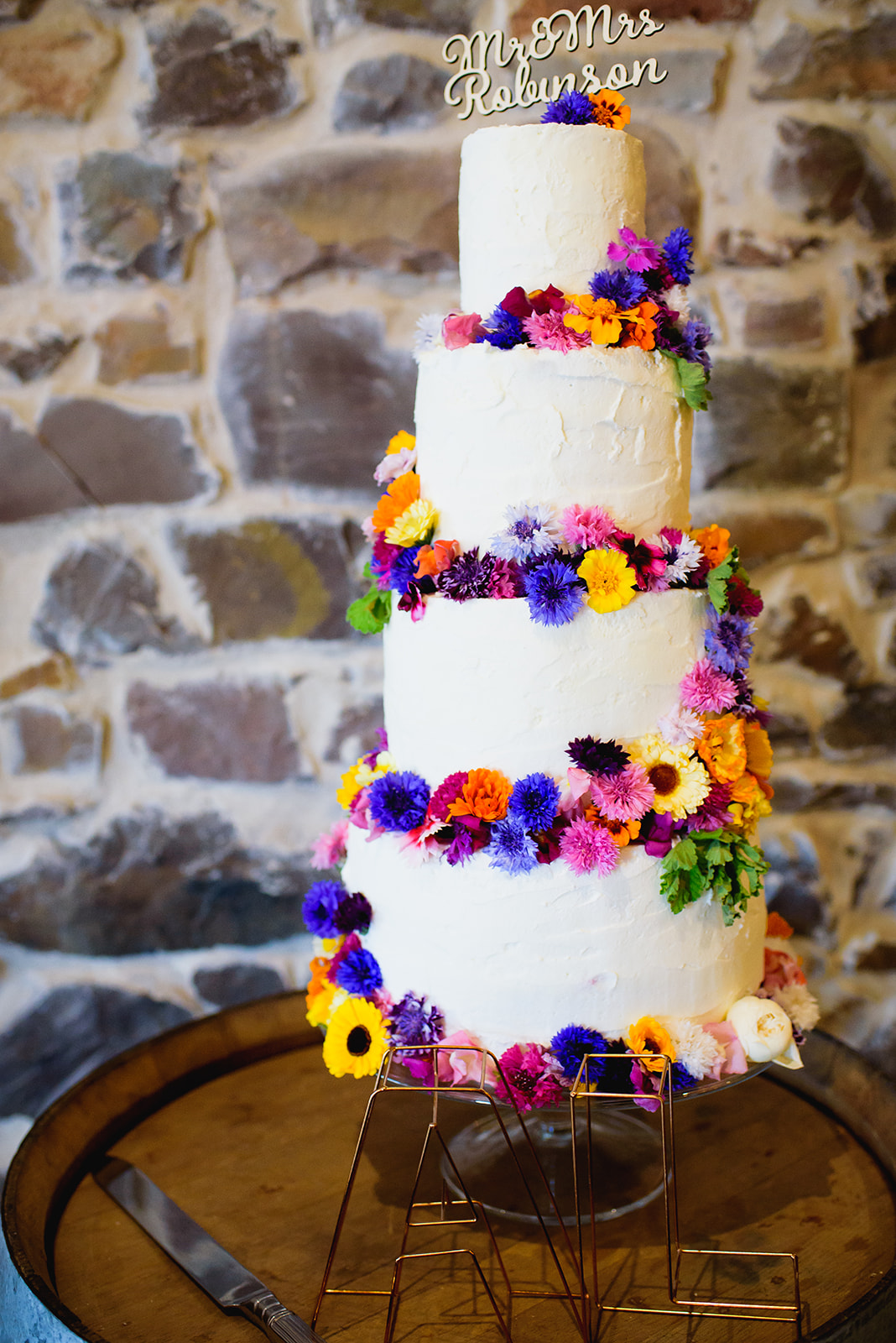 4 teired wedding cake adorned with bright flowers
