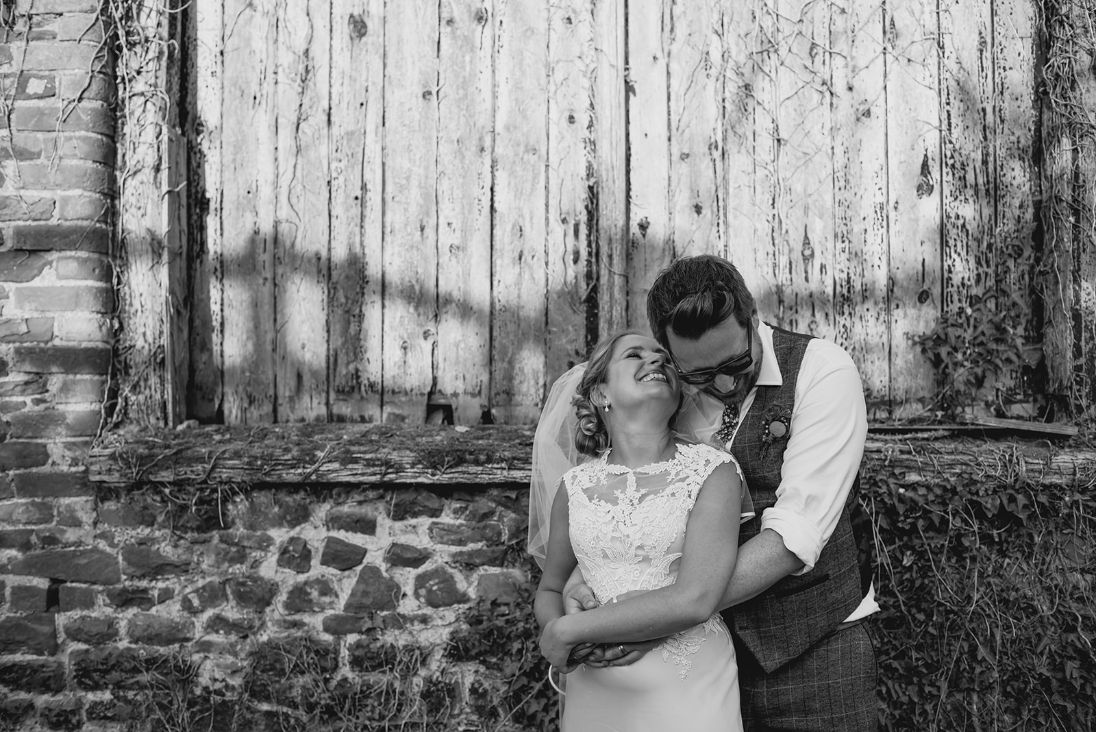 Bride and groom embrace and smile by old barn doors
